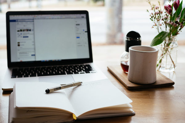 An open notebook on a desk with a laptop computer and coffee mug in the background