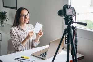 Woman sitting at her desk filming a video of herself using a digital camera